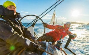 Action image of sailors on helm - Adventure Marine