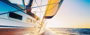 Boat under sail at sunset - Adventure Marine